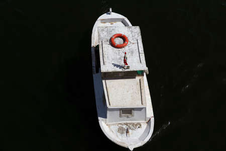 White fishing boat on a river in top view in high contrast image.