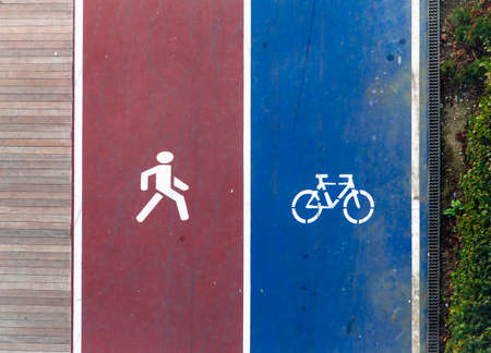 Walking and cycling icons on ground. Transport mode choice in contemporary cities. 免版税图像
