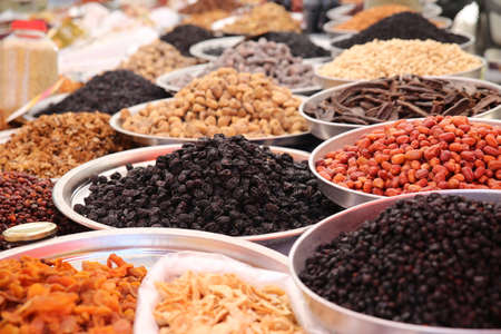 Close up of a variety of dried raisins and sultanas on display in large metal trays in a bazaar.