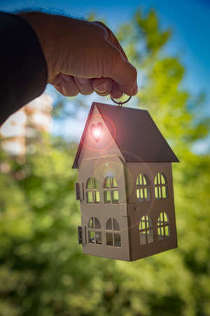 Housing opportunity concept with a house model hanging on the hand of a Middle-eastern man with lens flare coming out of a heart-shaped hole. 免版税图像