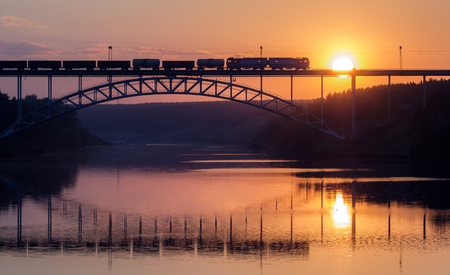 freight train rides on the railway bridge over the river during sunset, a summer evening the river Iset Stock Photo