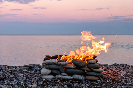 a fire burning in the stone place, beach and sea background Stock Photo