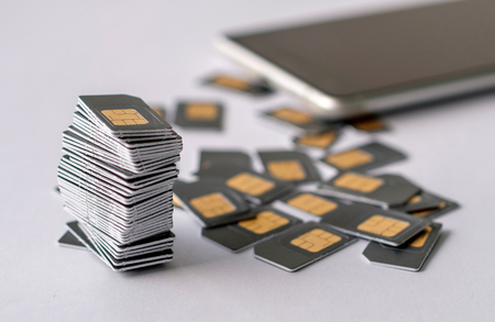 gray SIM cards are collected in a pile next to the scattered other SIM cards