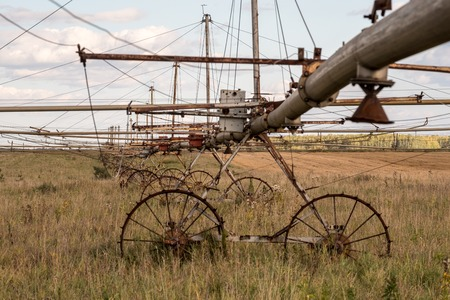 in the autumn the field of old rusty watering system fields, the system is broken