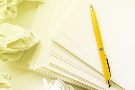 ballpoint pen near stack of paper, yellow tinted indoors Stock Photo