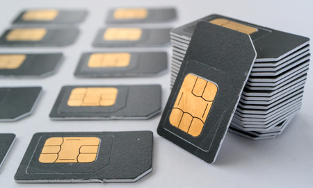 gray SIM card for phones gathered in a pile, lie close to a number of other cards, observing the rows