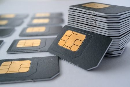 SIM cards for mobile phones in one stack leaning against the stack, gray card Standard-Bild