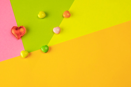 L'accumulo di cuori di plastica su pezzi di carta colorati, festivo di colore brillante, sfondo colorato