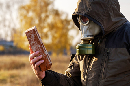 the man in the gas mask looks at the brick, a survey of dangerous infected objects careful examination, Russia Stock Photo