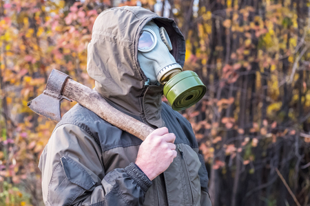 man in gas mask with an axe standing on a background of autumn leaves