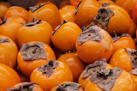 persimmon dusty and not washed out a multitude of orange fruits, healthy food Imagens