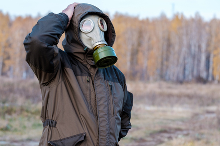 man in a gas mask in doubt and wonder whether, in the background autumn in Russia