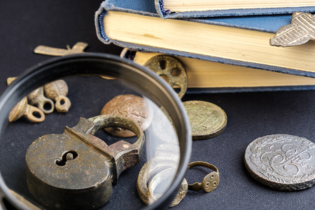 under a magnifying glass is considered an old copper padlock around an old coin and a book
