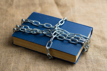 top view of a book in a blue cover lying on burlap, the book is wrapped in a chain, a forbidden Фото со стока