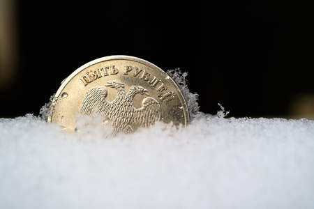 Russian money frozen in the snow, a metal coin in the snowdrift