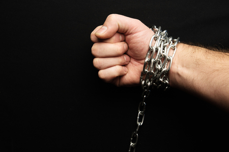 hand chained on a black background, silver metal Stock Photo