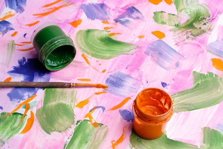 Two cans of paint gouache on the painted paper, a brush for drawing and an overturned container with Stock Photo