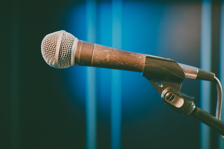 Singing into the microphone on stage, the microphone is mounted in the holder on a blue background