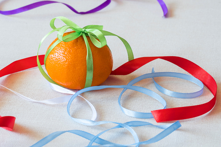a lot of different colored ribbons of different colors, one tied like a bractic on an orange, a citrus gift 写真素材 - 103118536