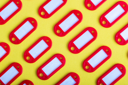 set of red tags for keys, diagonal direction on a yellow background Banque d'images