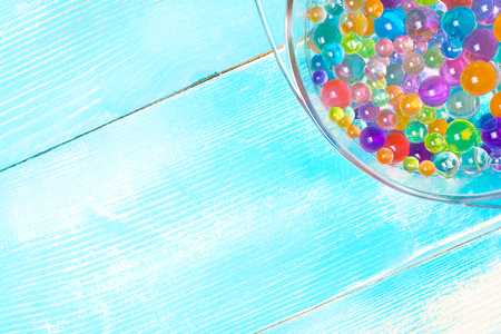 part of the plate with multi-colored hydrogel balls on a wooden blue background