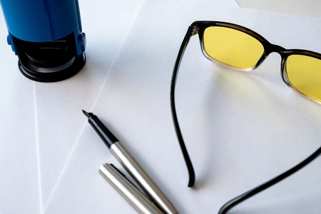 yellow glasses for a computer and a metal pen on a sheet of white paper, an office stamp for documents
