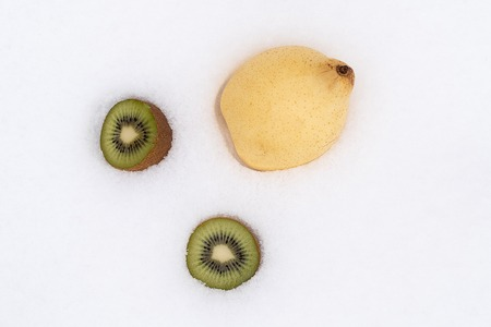 two kiwis of green color cut and one pear in the snow, different fruits in the snow