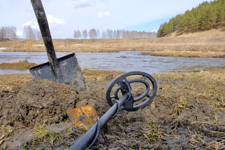 against the background of the spring gray forest and the river there are a shovel and part of a metal detector, freshly-grounded earth and tools for finding metal Imagens