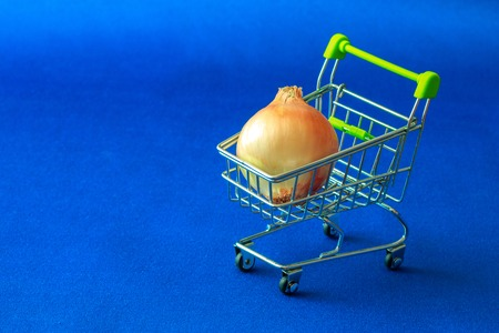 on a blue fabric background there is a basket from a supermarket in which they laid an unpurified bulb, yellow on blue Reklamní fotografie