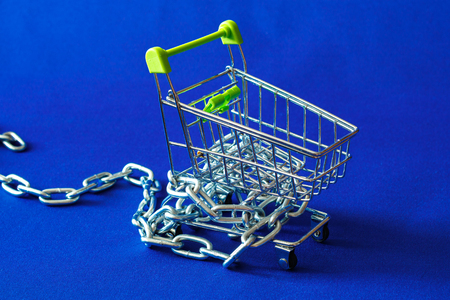 basket for purchases in which there is a metal chain, part of the chain fell to the floor, the background blue