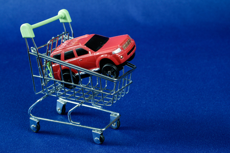 concept of car sales, red car in a supermarket basket on a blue fabric background, one red car