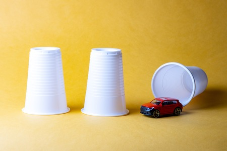 three plastic disposable cups on a yellow background, under one of them was hiding a car, guess where