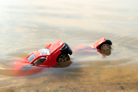 two front parts from two cars stick out of the water, drowned cars float, toy cars red