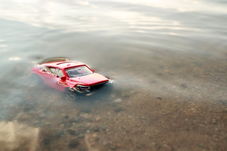 red toy car submerged in the water, drowned in the pond facing us, the accident in the summer on the beach Foto de archivo