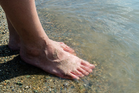 womens feet on the beach in the water coastline warm summer day, rest on the sea Stock Photo