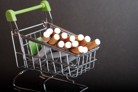 lots of cigarettes stacked in shopping basket filters to us, buying cigarettes wholesale, dark background