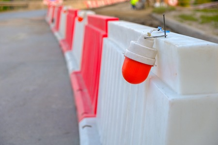 the red light on the plastic enclosure during the repair of the bridge, stretching into the distance plastic temporary fence