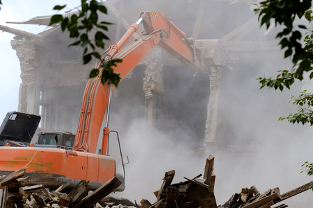 the boom of the excavator listed on the building which has been dismantled, the wall fell a lot of dust under the wheels of a tractor debris and stones, view through trees Imagens - 112457399