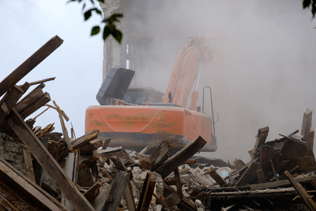 demolition of the building with the help of technology, dust and trees around the wreckage of the building under the wheels of the tractor