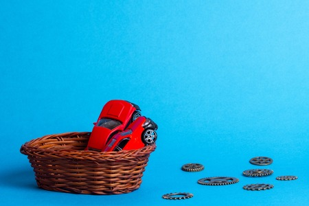 in a wicker basket of twigs are two red cars for children, next to the gears are made of metal