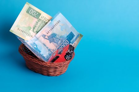 a gift in a wicker basket, money and a car in a hand-woven basket on a blue background, a birthday gift Stock Photo