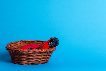 two red toy cars in a wicker basket on a blue background