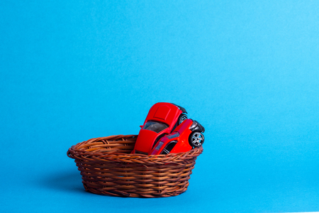 in the wicker basket are two red toy car models, the background is blue