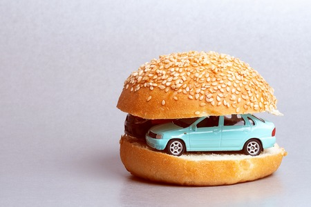 between halves of a bun from a hamburger there are cars toy, Breakfast from the car Stock Photo