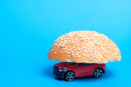 red toy car which is covered with one of the halves of the bun for sandwich, the background is blue