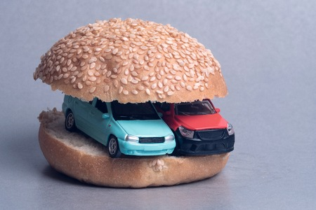 blue and red cars in a hamburger bun, gray background