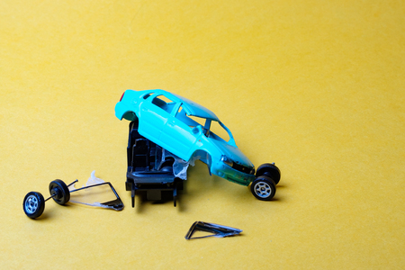 toy car broken into pieces, wheels and glass fell off, yellow background Reklamní fotografie