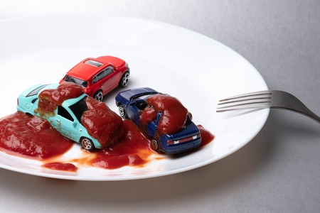 on a gray background there is a white plate on which there are three cars drenched with ketchup, on the edge of the plate there is a fork