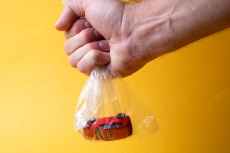a mans hand holds a plastic transparent bag in which a toy red car, yellow background Stock Photo