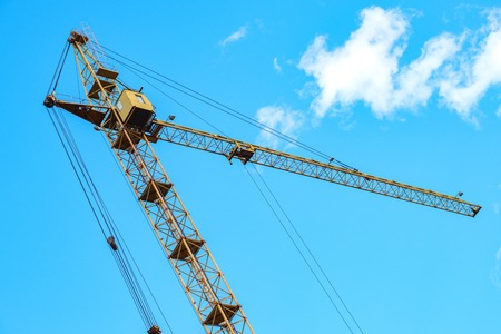 tilted to the left tower crane, the crane boom is directed to the right blue sky